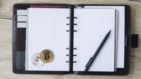Anteckningsbok av den Bitcoin gruvarbetaren Guld och silver Bitcoin och penna på en öppen anteckningsbok Fritt utrymme för satte  royaltyfri foto