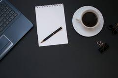Anteckningsbok, bärbar dator, penna och kaffe på kontorsskrivbordet Royaltyfri Fotografi