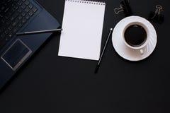 Anteckningsbok, bärbar dator, penna och kaffe på kontorsskrivbordet Arkivfoton