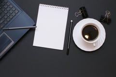 Anteckningsbok, bärbar dator, penna och kaffe på kontorsskrivbordet Fotografering för Bildbyråer