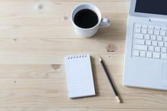 Anteckningsbok, blyertspenna, bärbar dator och kaffe på trätabellen Arkivfoto
