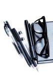 Anteckningsbok, blyertspenna och exponeringsglas Arkivfoto