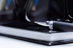 Anteckningsbok, blyertspenna och exponeringsglas Arkivfoton