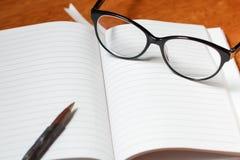 Anteckningsbok, blyertspenna och exponeringsglas Arkivbilder