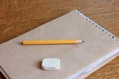 Anteckningsbok, blyertspenna och radergummi royaltyfria foton