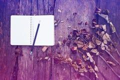 Anteckningsbok, blyertspenna och torkade rosor Arkivfoton