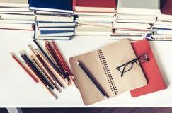 Anteckningsbok, blyertspennor, exponeringsglas och bunt av böcker, skolabakgrund för utbildning som lär begrepp arkivfoton