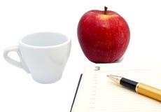 Anteckningsbok bollpenna, kopp, isolerat äpple Arkivfoto