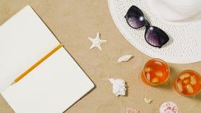 Anteckningsbok, coctailar, hatt och skuggor på strandsand stock video