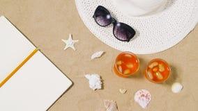 Anteckningsbok, coctailar, hatt och skuggor på strandsand arkivfilmer