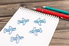 Anteckningsbok diagram i form av flygplan, penna, blyertspenna på en träbakgrund arkivfoto
