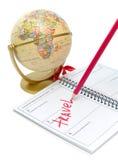 Anteckningsbok, en blyertspenna och ett jordklot på en white Arkivfoton
