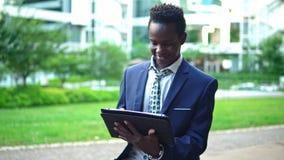 Anteckningsbok för bärbar dator för afrikansk amerikanaffärsmaninnehav som bär den blåa dräkten stock video