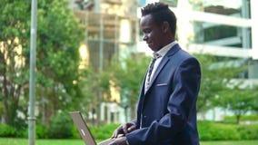 Anteckningsbok för bärbar dator för afrikansk amerikanaffärsmaninnehav som bär den blåa dräkten lager videofilmer