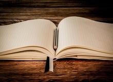 Anteckningsbok för fyrkantigt papper på trätabellen Arkivfoto