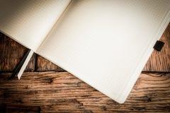 Anteckningsbok för fyrkantigt papper på trätabellen Royaltyfri Foto