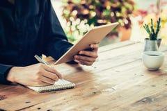 Anteckningsbok för handstil för hand för affärsman och innehavminnestavla i kaffe Arkivbild