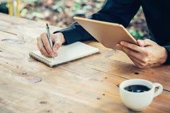 Anteckningsbok för handstil för hand för affärsman och innehavminnestavla i kaffe Royaltyfria Foton