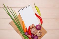 Anteckningsbok för kulinariska recept med nya organiska grönsaker Arkivfoto