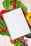 Anteckningsbok för kulinariska recept med nya organiska grönsaker Royaltyfri Fotografi