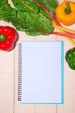 Anteckningsbok för kulinariska recept med nya organiska grönsaker Royaltyfria Foton