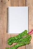 Anteckningsbok för kulinariska recept med nya organiska grönsaker Royaltyfri Foto
