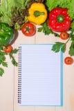 Anteckningsbok för kulinariska recept med nya organiska grönsaker Royaltyfria Bilder