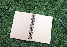Anteckningsbok för spiral för Kraft papper med pennan på den konstgjorda torvan arkivfoton