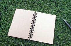 Anteckningsbok för spiral för Kraft papper med pennan på den konstgjorda torvan royaltyfri foto