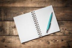 Anteckningsbok för tomt papper på brun trätabellbakgrund Top beskådar Fotografering för Bildbyråer