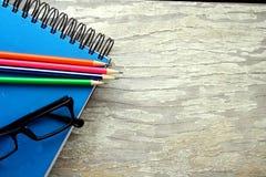 Anteckningsbok, glasögon och färgrika blyertspennor Royaltyfri Bild