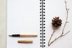 anteckningsbok, guld- penna och torr filial på skrivbordet, dekorerad tabell royaltyfri foto