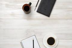 Anteckningsbok, kopp av coffe och pålagd tabell för blyertspenna Arkivfoton