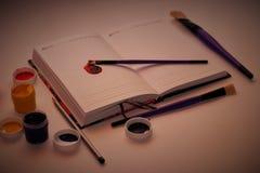 Anteckningsbok, målarfärg, borste och blyertspenna Fotografering för Bildbyråer
