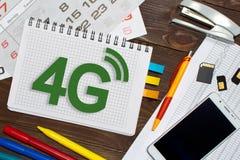 Anteckningsbok med anmärkningar 4G på kontorstabellen med hjälpmedel Royaltyfri Foto
