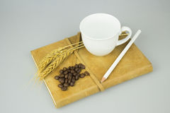 Anteckningsbok med blyertspenna- och kopp kaffeisolatbakgrund Royaltyfria Foton