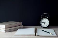 Anteckningsbok med blyertspennaklockan och böcker på tabellen Arkivfoto