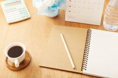 anteckningsbok med blyertspennan, kaffekopp, kalender, räknemaskin, flaskvatten Royaltyfria Foton