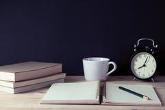 Anteckningsbok med blyertspennan, kopp kaffe i retro filter Royaltyfri Bild