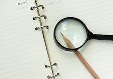Anteckningsbok med blyertspennan och exponeringsglas Royaltyfri Fotografi