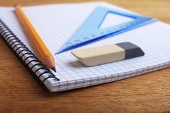 Anteckningsbok med blyertspennan och radergummit Arkivfoton
