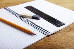 Anteckningsbok med blyertspennan och radergummit Arkivbild