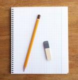 Anteckningsbok med blyertspennan och radergummit Royaltyfri Foto