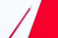 Anteckningsbok med blyertspennan på rött royaltyfri bild