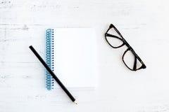 Anteckningsbok med blyertspennan på trä och exponeringsglas Arkivbild