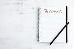 Anteckningsbok med blyertspennan på träbrunt Royaltyfri Bild