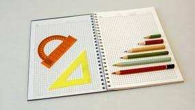 Anteckningsbok med blyertspennor och linjaler på en ljus bakgrund Royaltyfri Bild