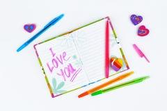 Anteckningsbok med brevpapper på en vit tabell Arkivfoton