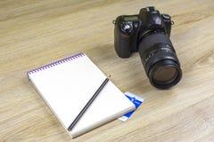 Anteckningsbok med den blyertspenna- och SLR fotokameran på wood textur arkivbilder