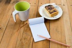 Anteckningsbok med den kaffekoppen och kakan Arkivfoton